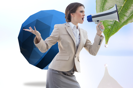 Furious stylish brown haired businesswoman shouting in a megaphone against drop on a leaf photo