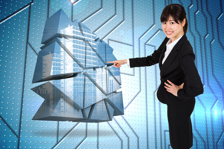 Smiling businesswoman pointing against circuit board on futuristic background photo
