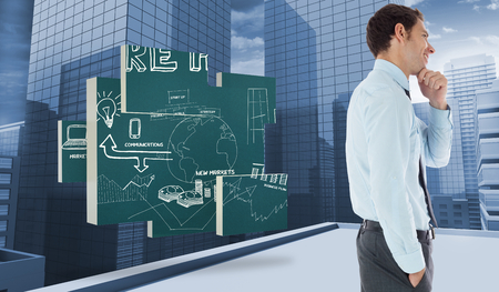 Thoughtful businessman with hand on chin against view of dull cityscape photo