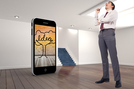 Thinking businessman holding pen against digitally generated room with stairs photo