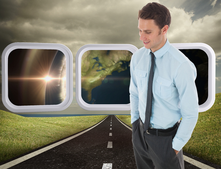 Happy businessman standing with hand in pocket against highway under cloudy sky photo