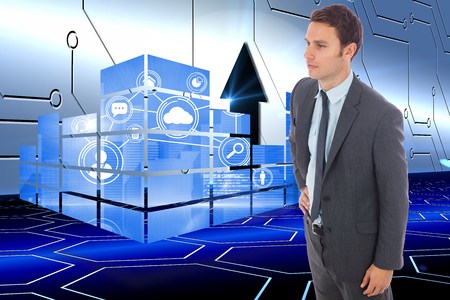 Serious businessman standing with hand on hip against arrow on technological background photo