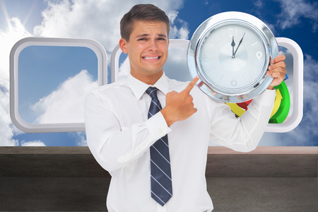 Anxious businessman holding and showing a clock against balcony and cloudy sky photo