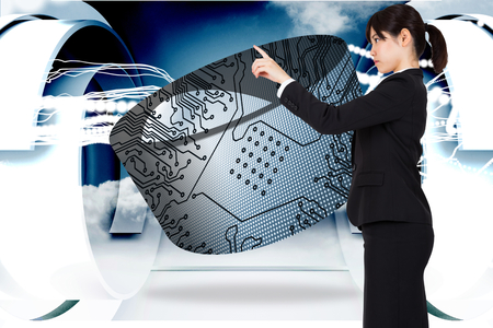 Serious businesswoman pointing against white lines with cloud design on a futuristic structure photo