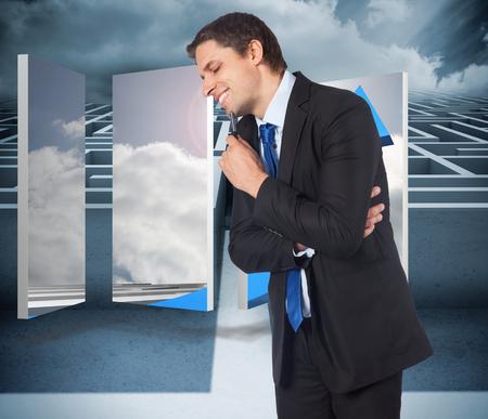 Thinking businessman holding pen against big 3d maze under clouds photo