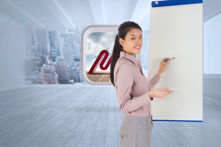 Businesswoman painting on an easel against city scene in a room photo