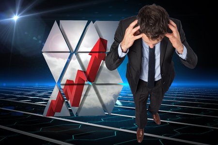 Stressed businessman with hands on head against circuit board on futuristic background photo