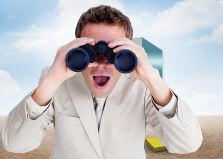 Positive businessman using binoculars against colorful arrows in a desert landscape photo