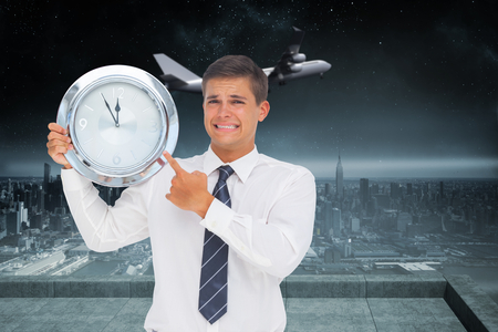 Anxious businessman holding and showing a clock against balcony overlooking city photo