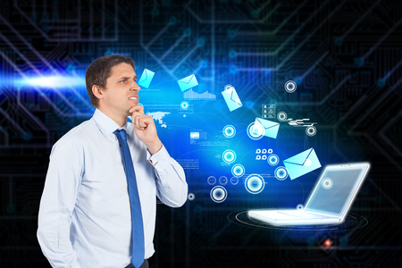 Thinking businessman touching his chin against futuristic black and blue background photo