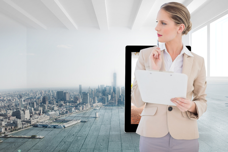 Pensive blonde businesswoman holding clipboard against city scene in a room photo