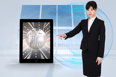 Focused businesswoman pointing against abstract blue design in white room photo