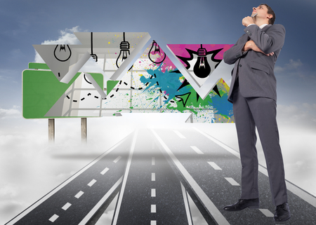 Thoughtful businessman holding pen to chin against roads over clouds with empty signposts photo