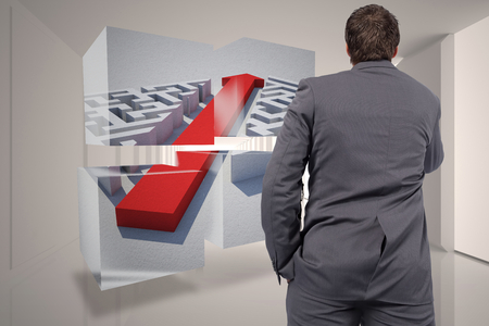 Thinking businessman against tiny figures in bright room photo