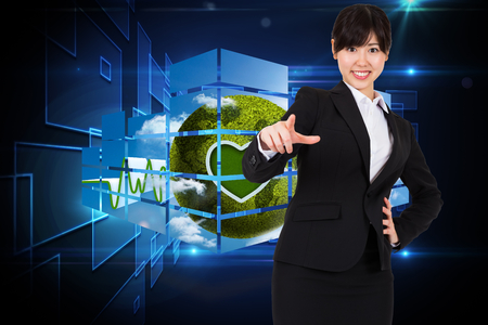 Smiling businesswoman pointing against black background with shiny squares photo
