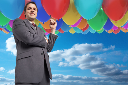 Thoughtful businessman holding pen against balloons in the sky photo