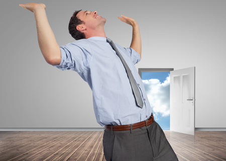 Businessman standing with hands up against door opening showing blue sky photo
