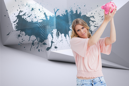 Disappointed woman holds a piggy bank up over her head against splash on wall revealing technology graphic