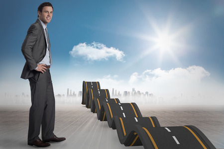 bumpy road: Smiling businessman with hands on hips against bumpy road leading to city
