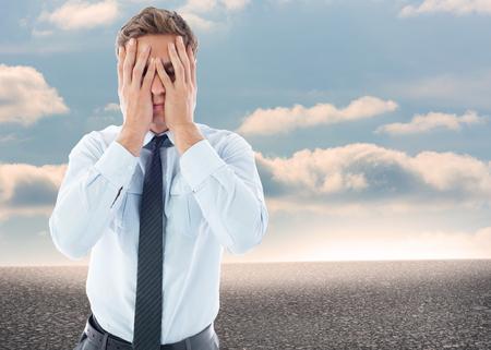 Businessman with a headache against desert landscape with blue sky Stock Photo