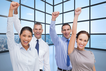 Cheerful work team posing with hands up against room with large window showing city photo