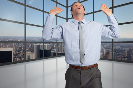 Businessman standing with arms pushing up against room with large window showing city photo