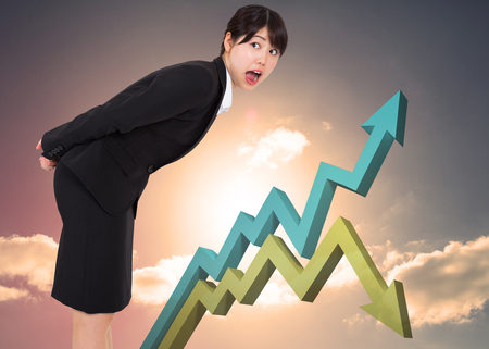 Surprised businesswoman bending against blue and green arrows against blue sky photo