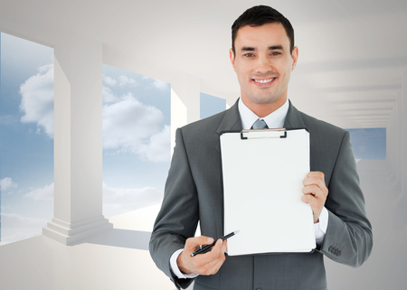 Businessman pointing with pen on clipboard against bright white hall with columns photo