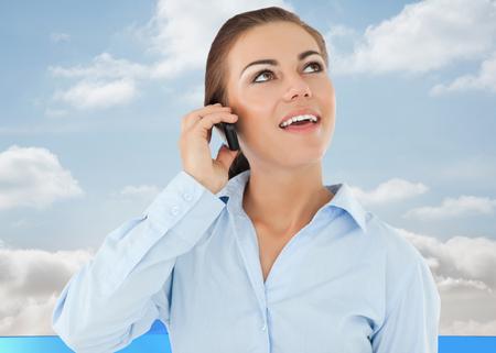 flechas curvas: Empresaria sonriente que mira hacia arriba, mientras que en su tel�fono contra flechas curvas azules apuntando contra el cielo Foto de archivo