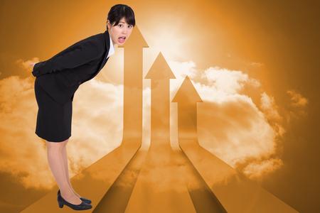 Surpised businesswoman bending against arrows in the sky in orange photo