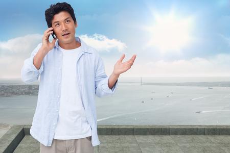 clueless: Clueless male on his cellphone against coastline city