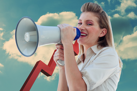 Beautiful businesswoman shouting through megaphone against red arrow pointing down against sky photo