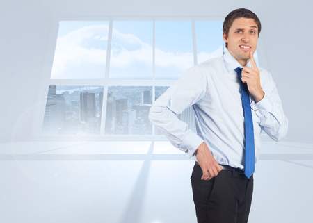 Thinking businessman touching his chin against bright white room with windows photo