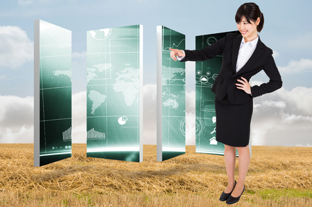 Smiling businesswoman pointing against bright brown landscape photo