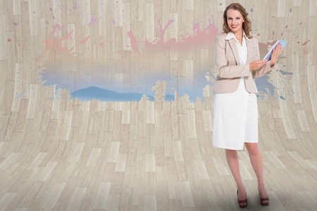 Happy pretty businesswoman holding a tablet pc against splash showing desert landscape photo