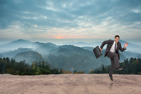 Happy businessman in a hury against scenic countryside with mountains photo