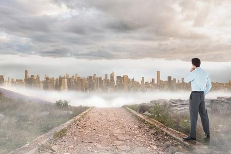 urban sprawl: Thoughtful businessman with hand on chin against stony path leading to large urban sprawl Stock Photo