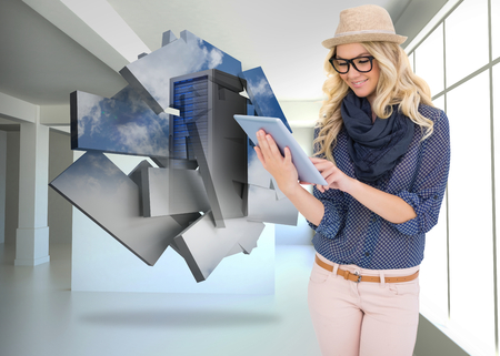 Smiling trendy blonde using tablet computer against white room with screen photo