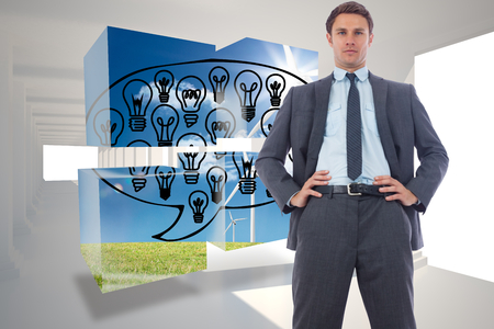 Stern businessman with hands on hips against digitally generated room with columns photo