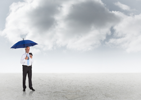 Happy businessman holding umbrella against cloudy sky background photo