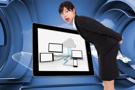 Surprised businesswoman bending against white cloud design on a futuristic structure photo