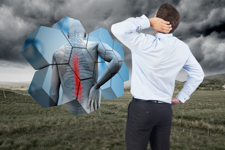 Thinking businessman scratching head against stormy countryside background photo