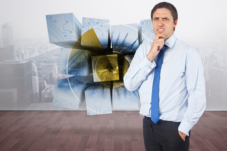 Thinking businessman touching his chin against city scene in a room photo