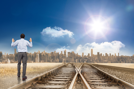 Businessman posing with hands up against train tracks leading to city under blue sky photo