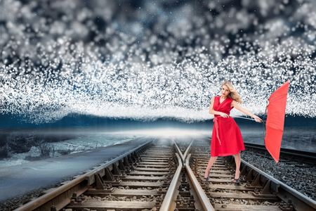 Elegant blonde holding umbrella against train tracks under blanket of bright stars photo