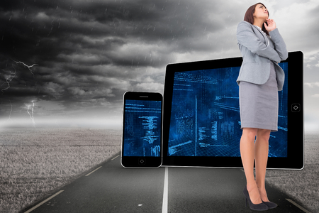 Focused businesswoman against stormy landscape with street photo