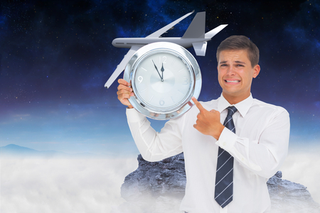 Anxious businessman holding and showing a clock against rocky landscape photo
