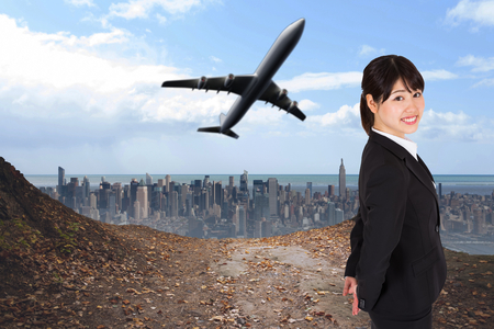 Smiling businesswoman against large city on the horizon photo