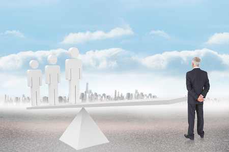 Rear view of mature businessman posing against white human resource scales in front of city photo