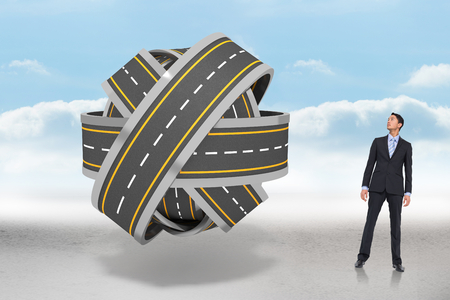 tangled roads: Serious asian businessman  against tangled roads in a ball Stock Photo